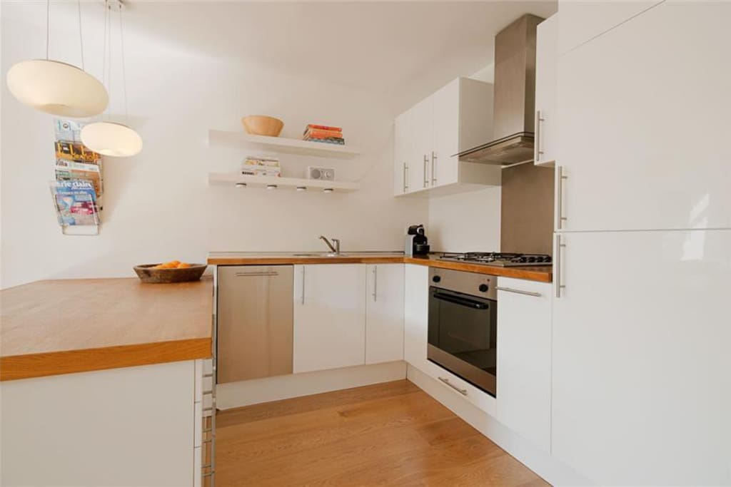 Kitchen equipped with dishwasher, stove, oven and kettle.