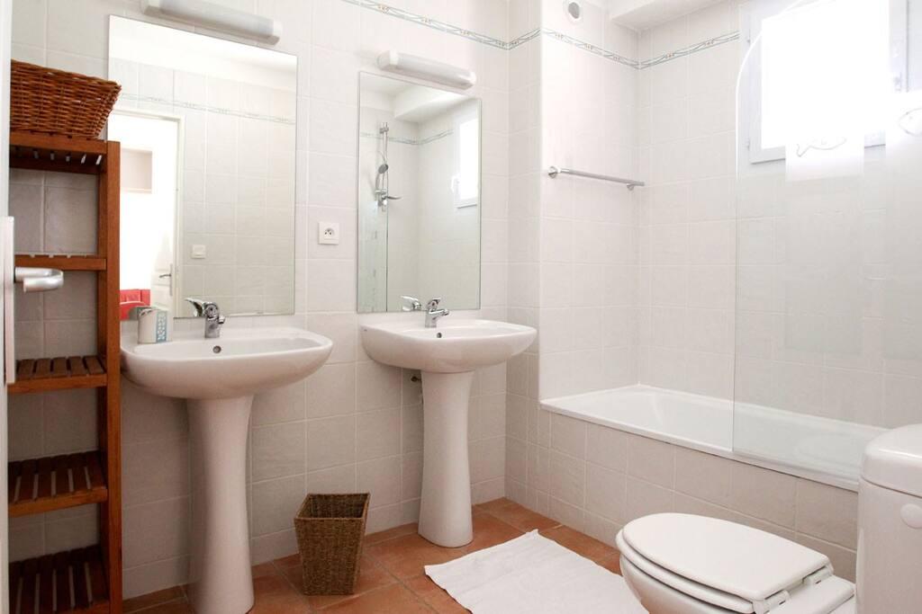 une salle de bain avec baignoire et 2 lavabos
