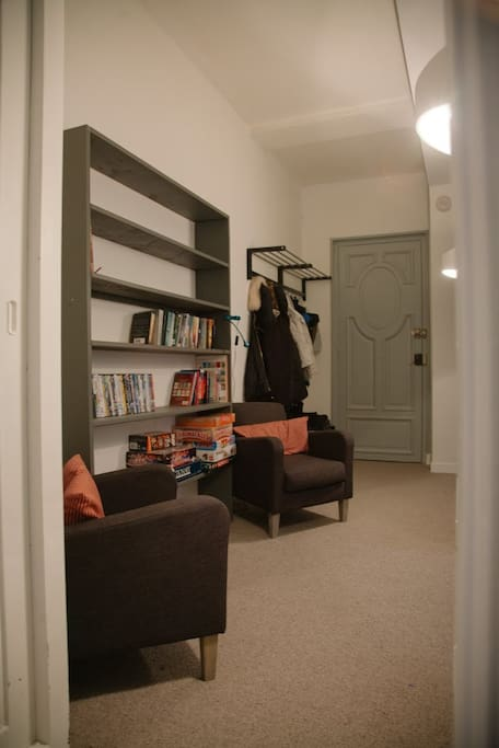 The hallway and reading area with shelves packed with books, games and DVDs.
