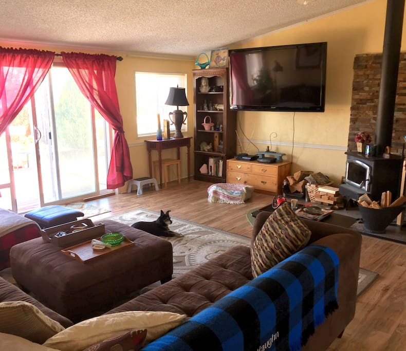 Living room with wall mounted TV and wood stove, A/C and ceiling fan.