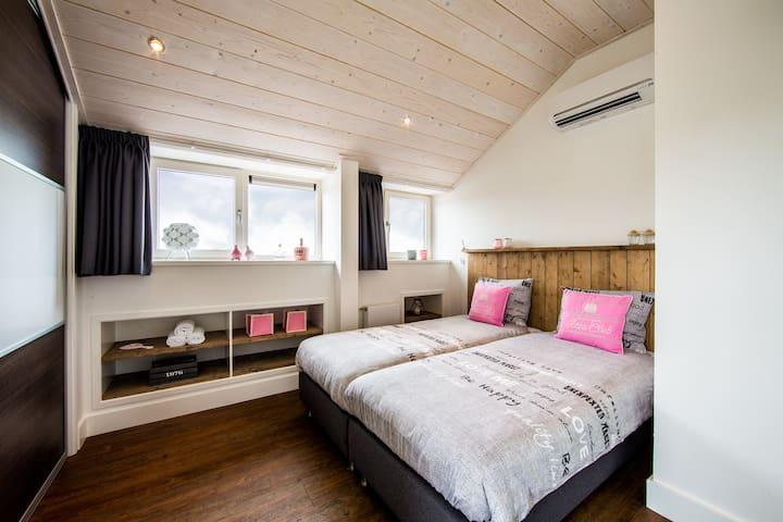 Slaapkamer 6 (1e verdieping) met eigen badkamer (stortdouche, wandmeubel en toilet).