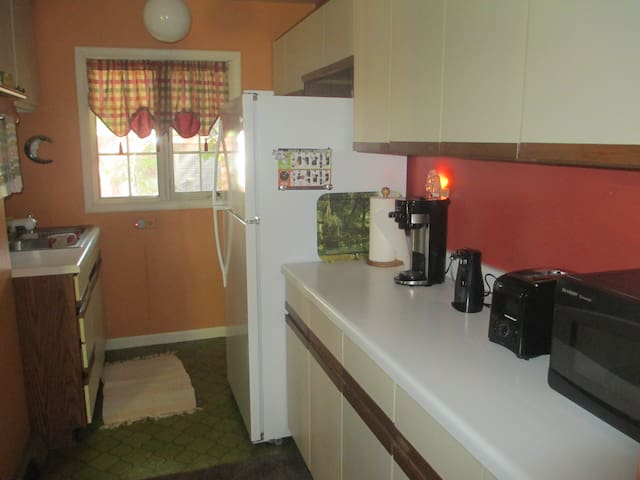 A full-size fridge, a Keurig style coffee maker, a can opener, a toaster, a microwave, and a stove/oven all available for use.