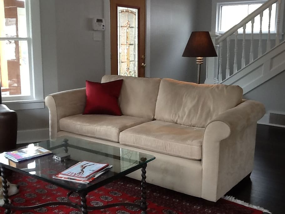 The living room contains a comfortable couch with a big TV facing it.