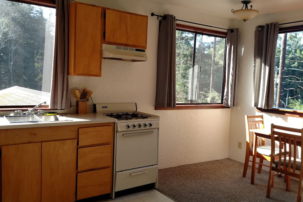 Kitchen complete with stove, sink, refrigerator, microwave, coffee pot and tea kettle.