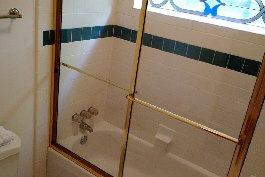 Natural lighting through stained glass window in the shower.