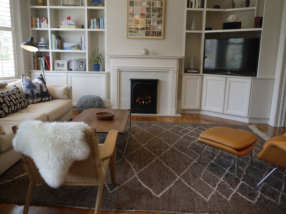 Living room with a gas fireplace, antique Moroccan rug, and art/design books
