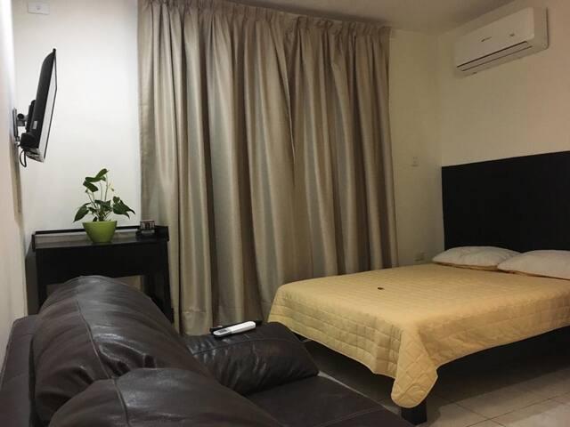 Cálida habitación con una cama matrimonial y un sofá de piel para tu descanso, además cuenta con Smartv con cuenta de Netflix activa para que puedas disfrutar tus series y películas favoritas.