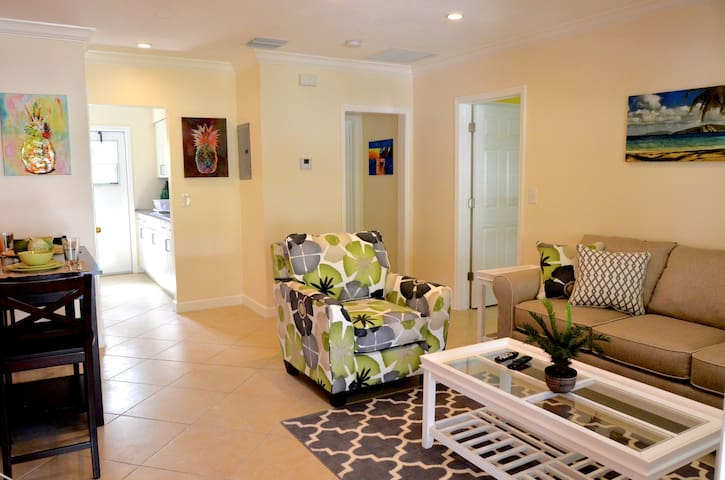 Open living room with flat screen TV, sofa bed, dinner table, and kitchen.