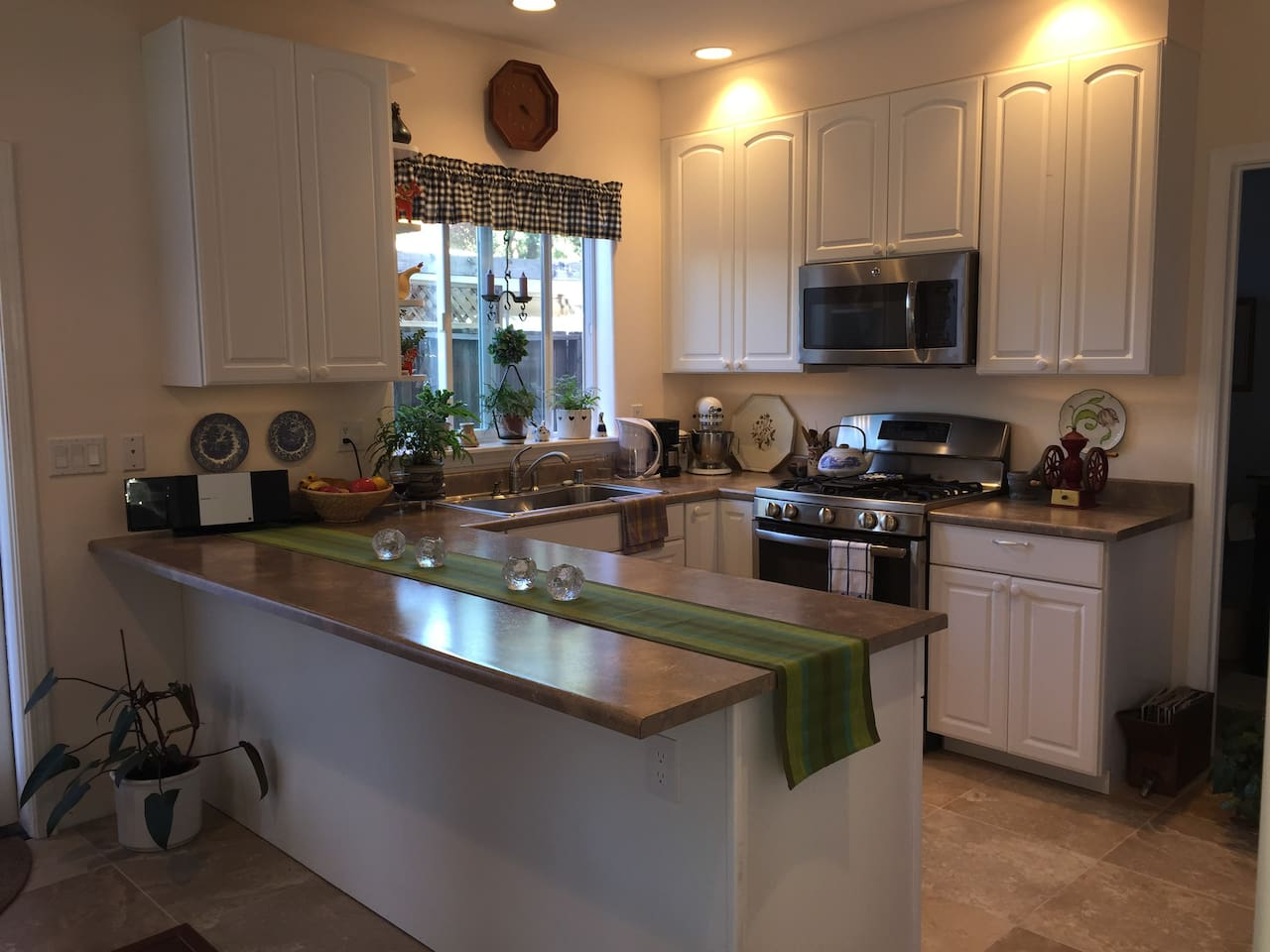 U-shaped kitchen counter with gas range, microwave and tile floor.