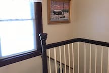 Top of the stairs to the second floor. Beautiful local art work is through out the home.
