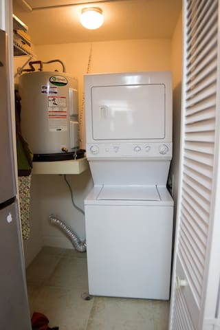 Stackable Washer/Dryer with Laundry Detergent in the kitchen area.