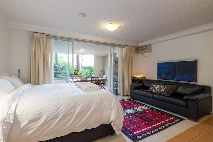 What a cute and comfy studio apartment! You can watch the BIG screen TV in bed.