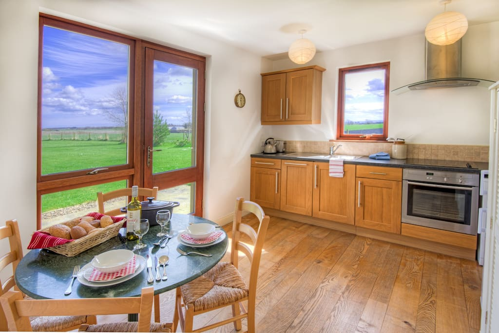 Kitchen, Garden Cottage, Scottish Borders. With French doors with views of the surrounding countryside, dishwasher, microwave, cooker, fridge-freezer and loads of kitchen equipment.