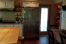 Large refrigerator and pantry. Door leads to outdoor patio area and grill.