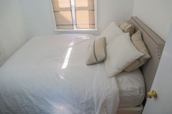 A different view of the queen-sized bed, with new linens.