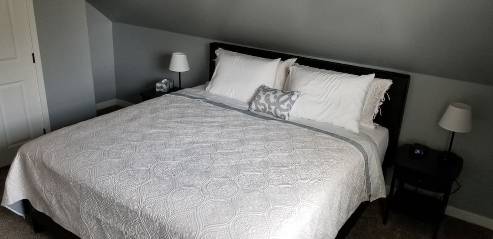 Master king bedroom with a spacious closet w/ hangers, lamps, alarm clock with USB charging ports, suitcase rack, suitcase storage nook, and door lock.