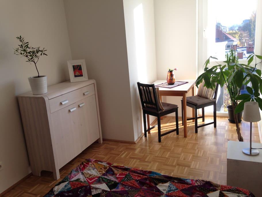 Vollmöbliertes Zimmer mit Tisch, Stühlen, Kommode, Bettkasten und Kleiderschrank