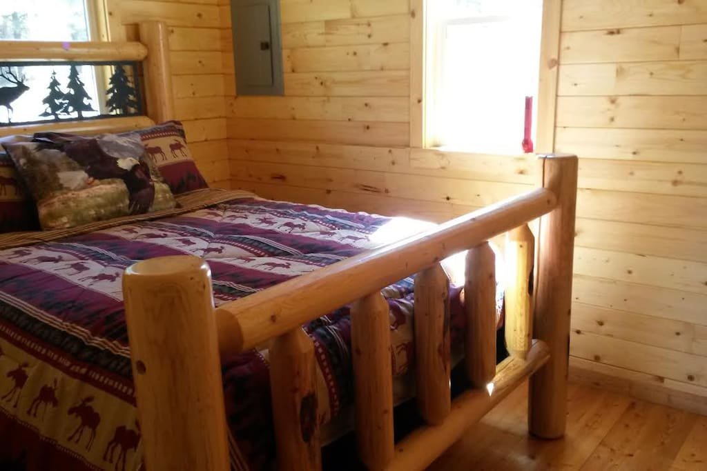 Queen Size log bed in pine lined room with ceiling fan