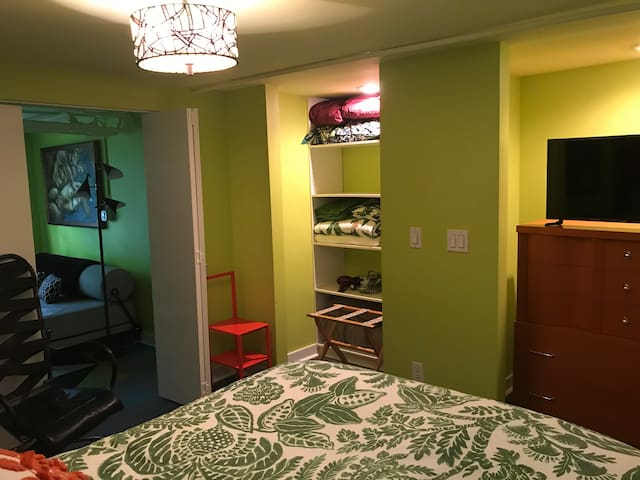 Bedroom has large smart TV and dresser and closet for storing clothing.