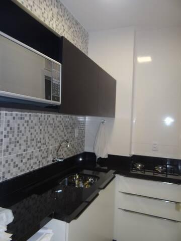 Cozinha com microondas, frigobar, cooktop, armários, equipada com utensílios de cozinha.