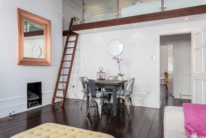 Living room with fixed ladder leading to mezzanine level