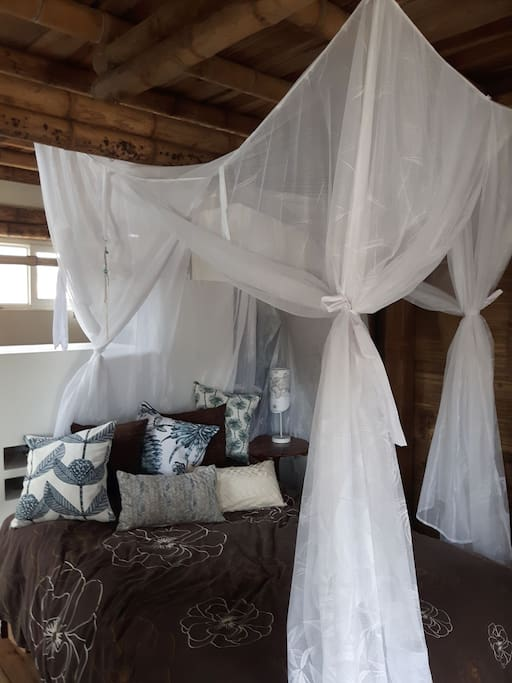 Super comfy bed with full length mosquito net and lots of pillows and white quality sheets.