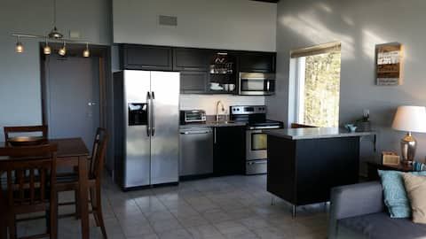 Open concept kitchen, filled with light and featuring fully stocked cabinets with place settings for four!
