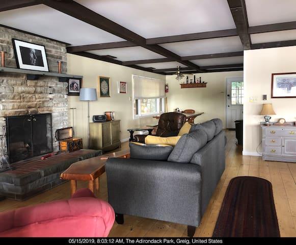 Great room, w large fireplace 2 sofa's and game table DVD's in green chest, VCR's in gray chest