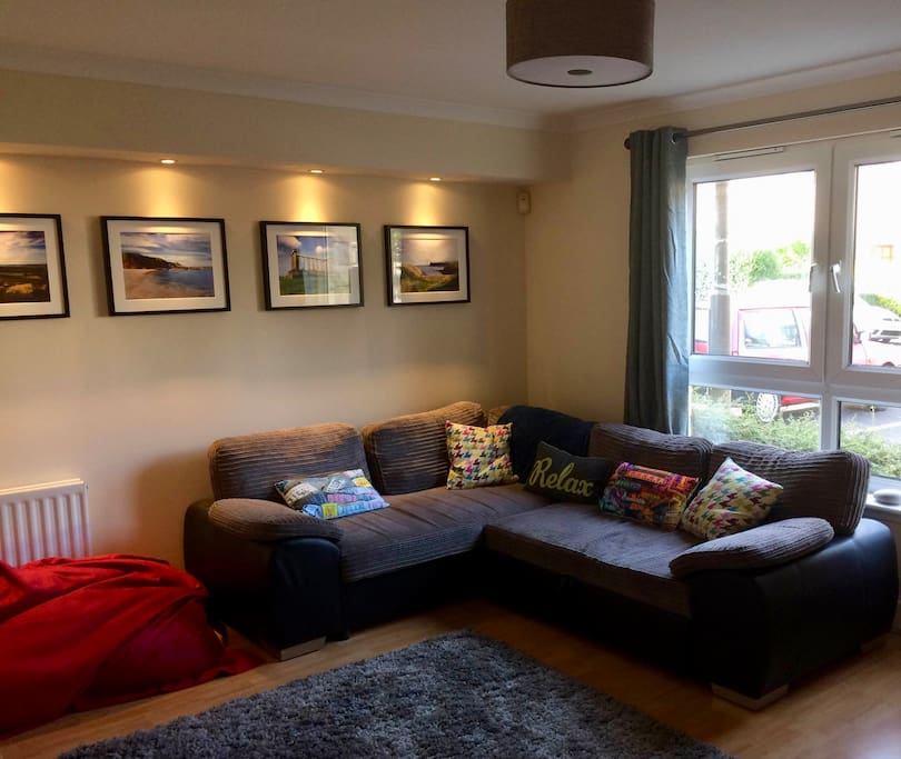 Cosy living/dining room with corner sofa, feature lighting and bean bag