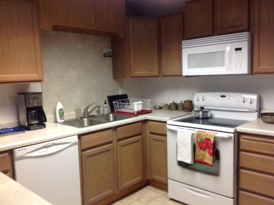 Kitchen with microwave, toaster, coffee maker, stove.