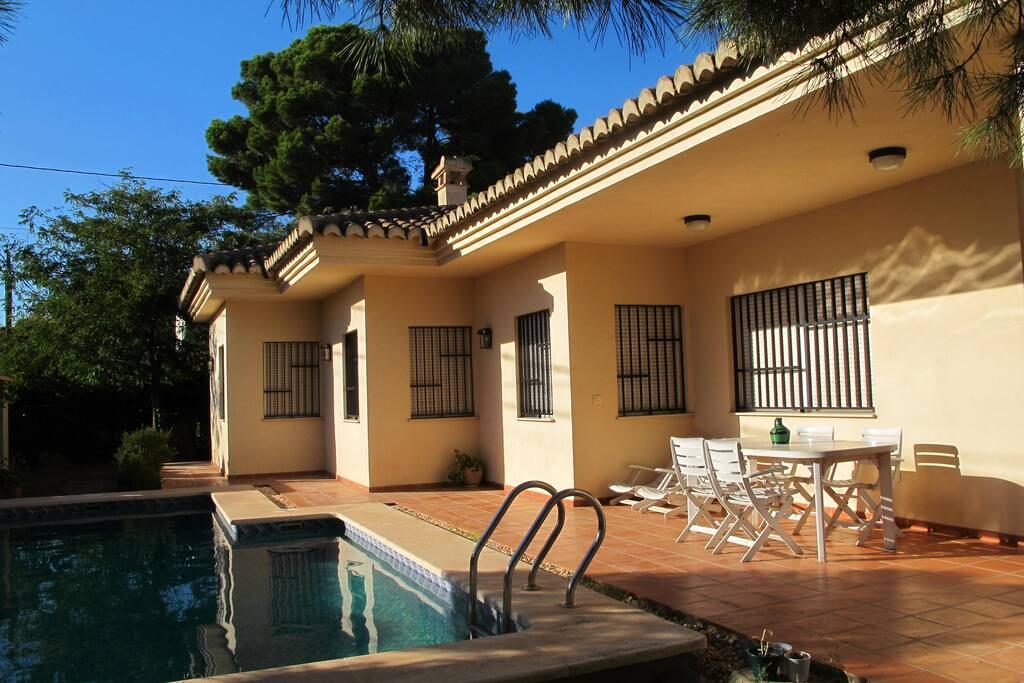 Junto a la piscina hay una mesa con 4 sillas además de 2 tumbonas.