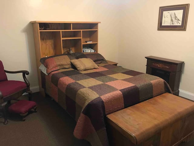 Double bed in bedroom on right. Electric fireplace.