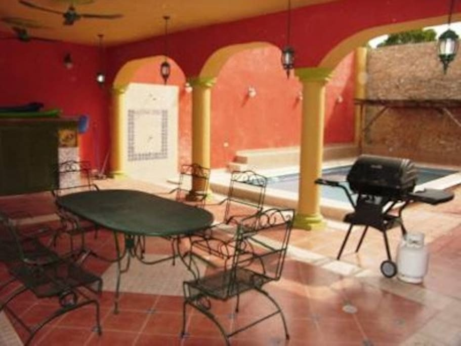 Covered patio by pool area with grill and outdoor shower