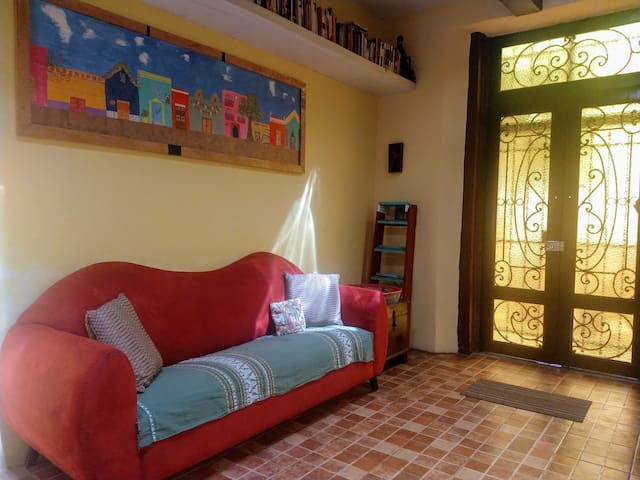 """Front door and living room. """"The pictures still don't completely reflect how truly beautiful this home is in the spaciousness, good vibes and beautiful artistic style with an emphasis on local architecture."""" --Sarah"""