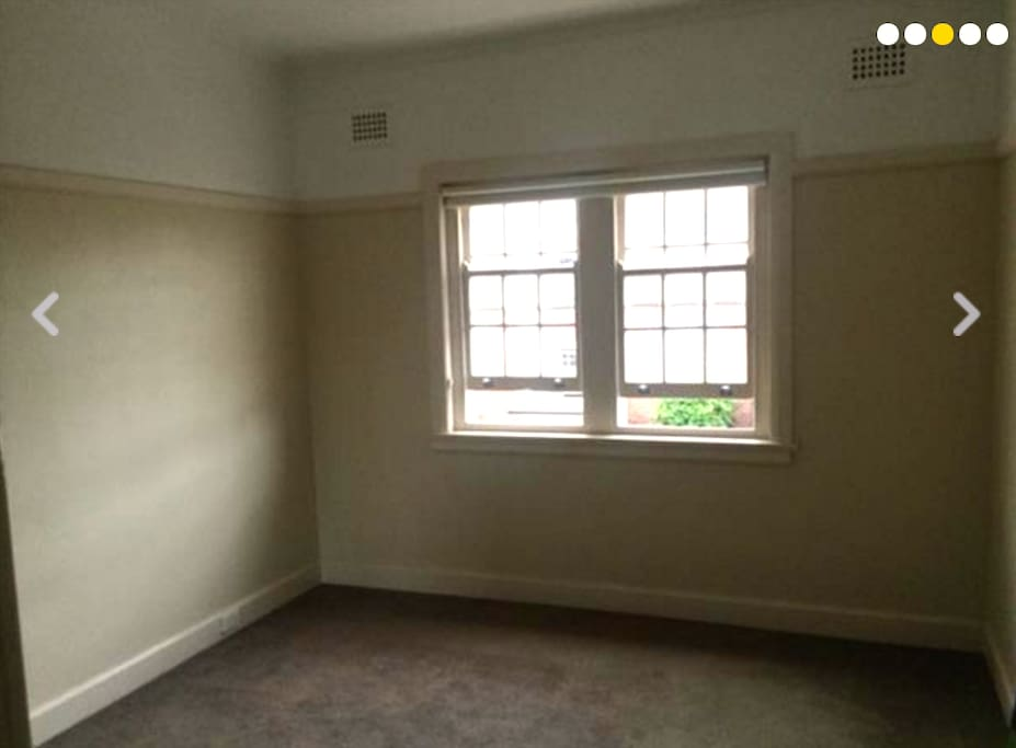 Large sunny bedroom with carpeted floors and blinds