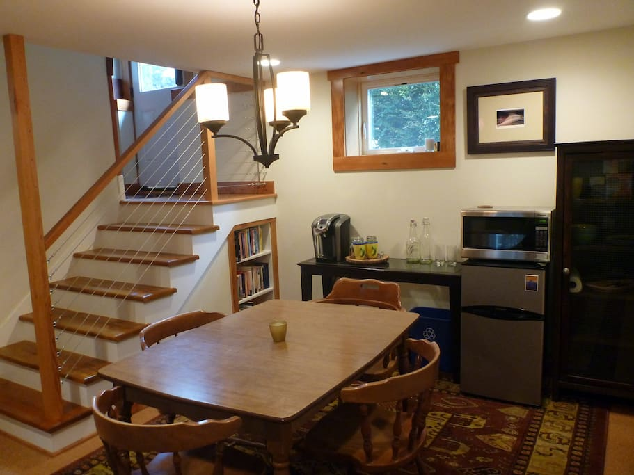 This is the south side of the den-- enjoy a cup of complementary coffee or tea, filtered water, use the fridge or microwave, peruse local hiking books for places to go, play cards or work at the table, connected by blazing fast wifi