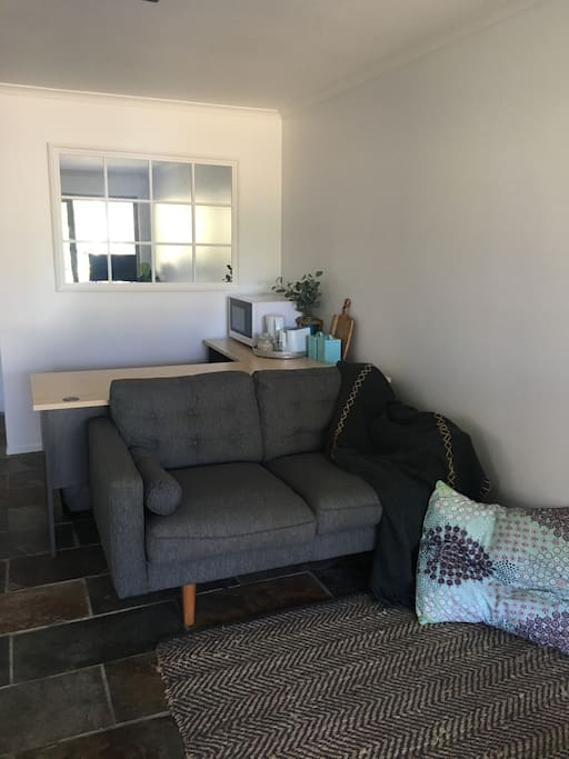 Lounge room features modern couch, flat screen tv, microwave, bar fridge, kettle & toaster. Lounge room looks out to gardens & sand dune