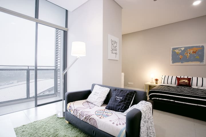 A generous living & bedroom area with a view of the city.