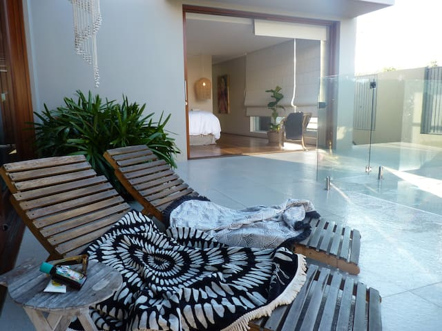 Soak up the sunshine in the northerly aspect closeby the salt water crystal  inground pool surrounded by tropical gardens