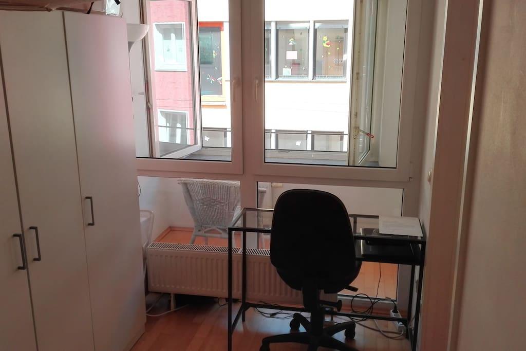 Schreibtisch im Schlafzimmer mit Kleiderschrank, Ausblick auf Loggia