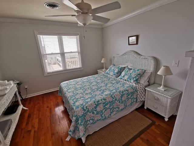 Ocean view bedroom with queen bed and tv