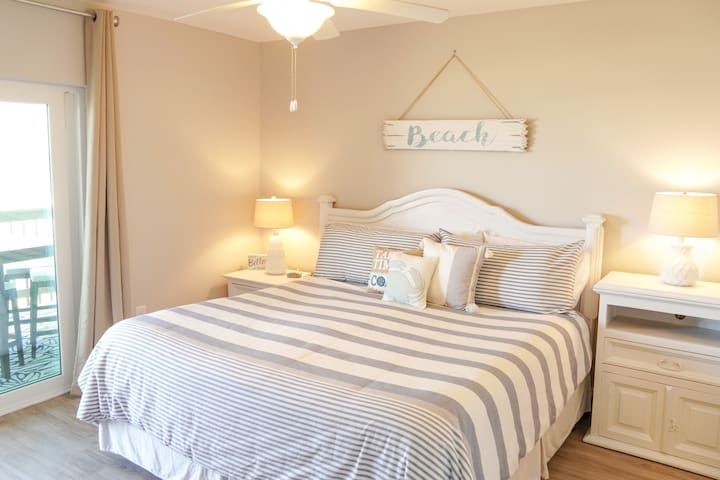 """""""The Beach Room"""": Bright master bedroom w/ King bed, sliding glass door to the private patio + ocean views, blackout curtains, and ceiling fan"""