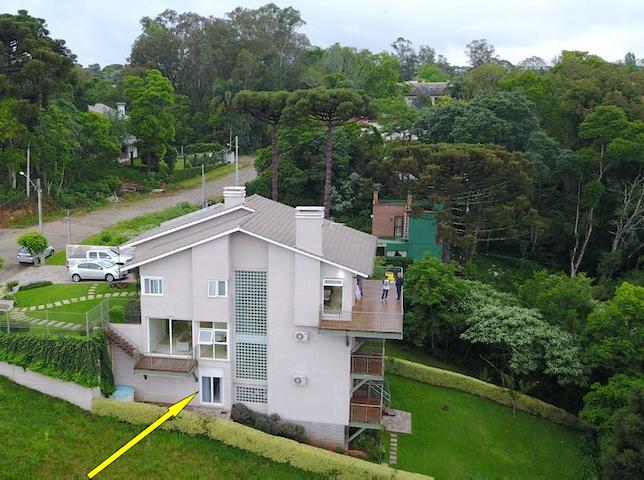 Foto aérea da residência. A seta indica a localização da suíte Alfazema na casa, com acesso direto ao bosque.