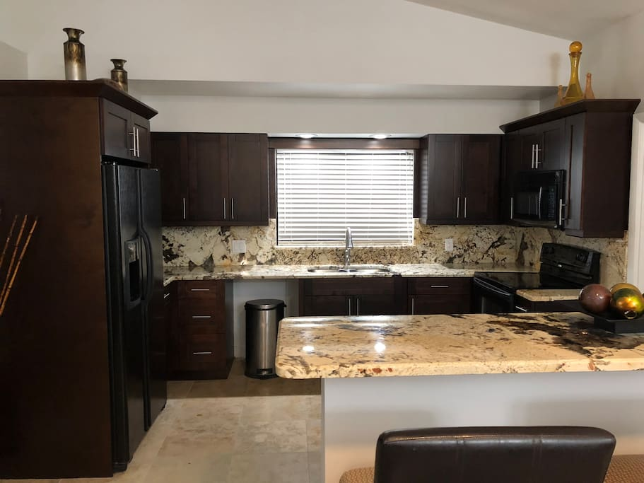 Beautiful exotic marble counter tops and full backs splash on brand new all wood cabinets.