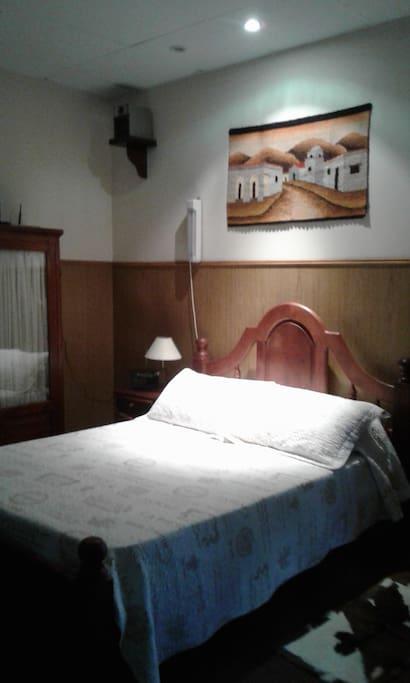 Cama matrimonial con dos mesas de luz y alfombras de pie