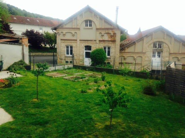 Un jardin avec vue sur le pressoir Veuve Cliquot
