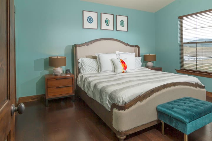Master bedroom with king Tuft & Needle mattress, CubieBlue Bluetooth speaker/alarm clock, and balcony access