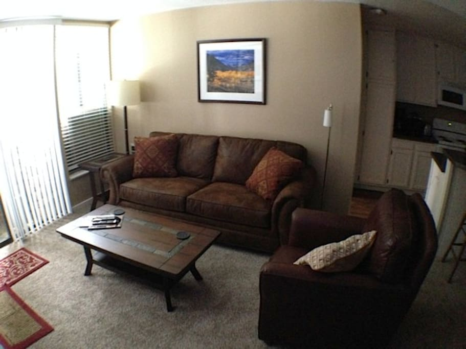 Living room has a fold out couch, balcony and fireplace.