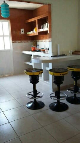 Cocina con desayunador, equipada con lo básico para la preparación de alimentos;  platos, vasos y cubiertos.  Refrigerador, estufa, horno de microondas y licuadora.