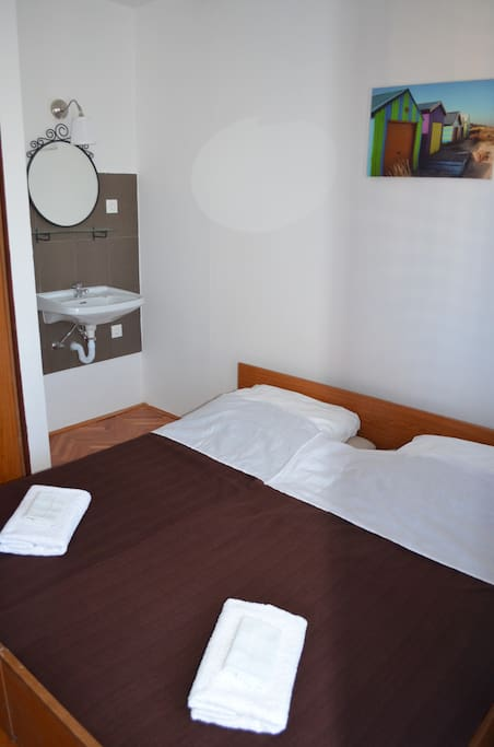 Double bed in airy and cozy room with its own sink